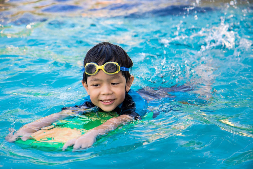 Young boy wearing rash vest, bathers and goggles. Pictured swimming and using a kickboard.