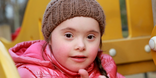 Young girl with down syndrome giving thumbs up and playing at outdoor playgound