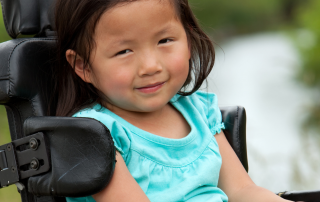 Young asian girl in wheelchair pictured outside