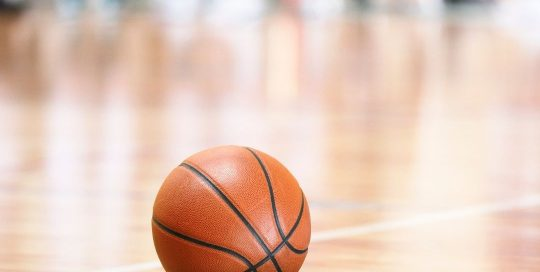 Basketball resting on floor in middle of indoor court
