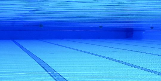 Swimming pool with shot taken from beneath the surface showing lanes lines on bottom of pool